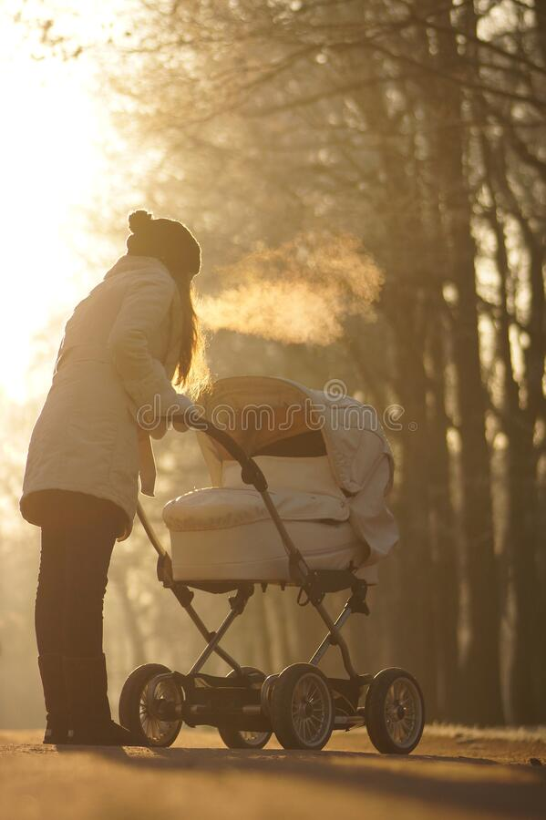 Silhouette of young woman on sunny footpath and looking at child in baby stroller. Winter park, childcare and love. Silhouette of young woman in white coat and royalty free stock photos