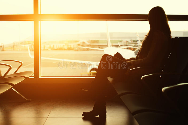 Silhouette of a young woman traveler waiting at the airport for departure stock photo