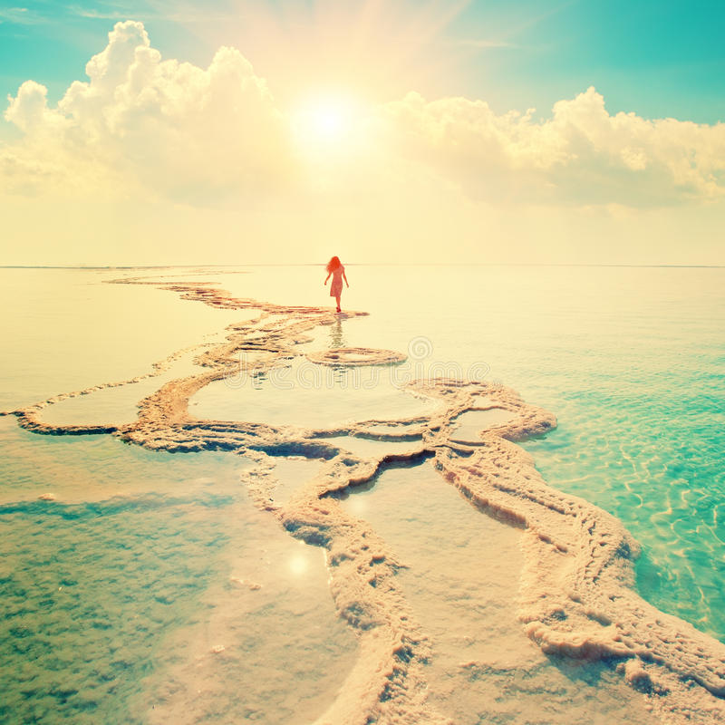 Silhouette of young woman walking on Dead Sea stock photos