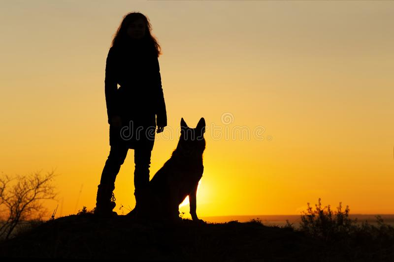 Silhouette of young woman walking with a dog in the field at sunset, pet sitting near girl`s leg on nature, figure of friends in. Heroic pose, human and animal royalty free stock photo