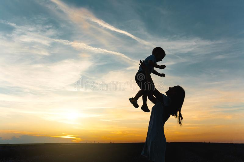 Silhouette of young woman high toss up little cute child baby boy on nature, sunset horizon background. Mother throw up stock photos