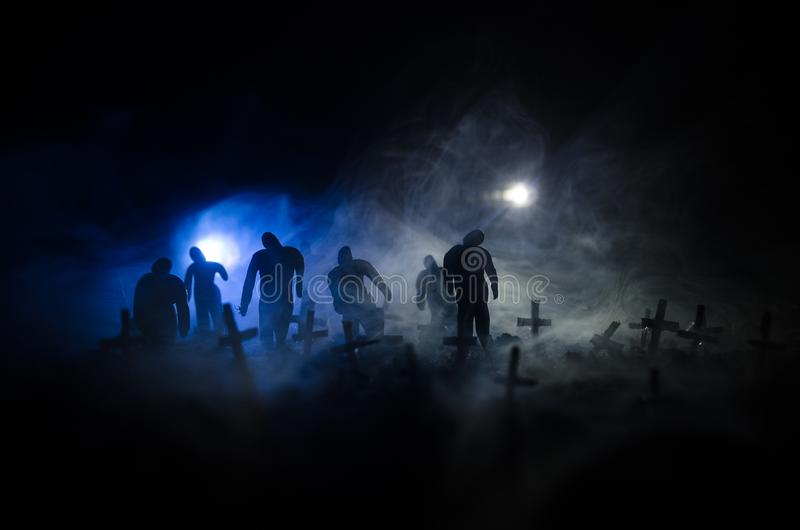 Silhouette of zombies walking over cemetery in night. Horror Halloween concept of group of zombies at night royalty free stock photography