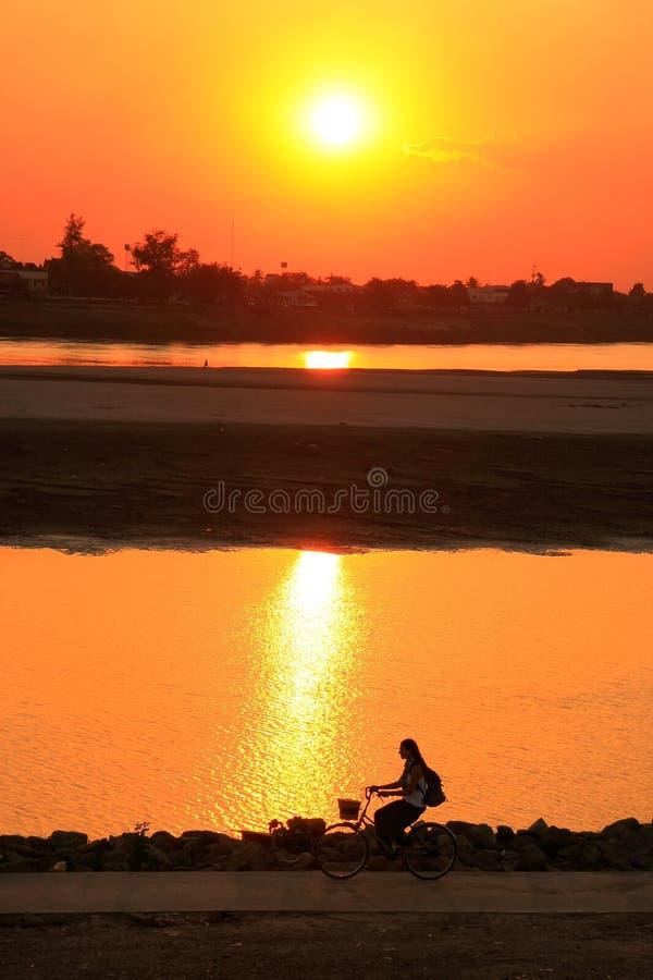 Silhouetted катание женщины на Меконге стоковое фото rf