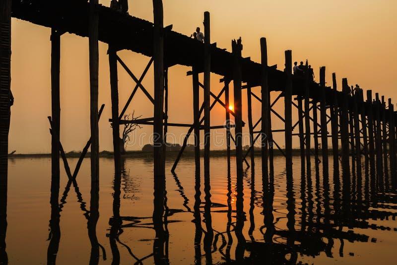 Silhouetted люди на мосте на заходе солнца, Amarapura u Bein, области Мандалая, Мьянме стоковое изображение