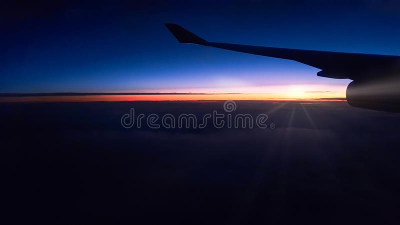 Silhouetted airplane wing during a night flight stock images