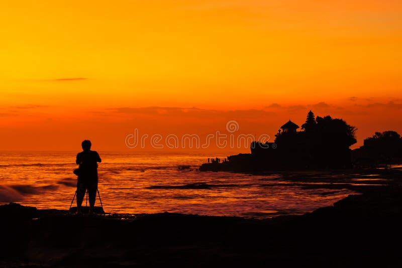 Silhouetted av fotograf och den Tanah lotten på solnedgången, Bali, Indon arkivbild