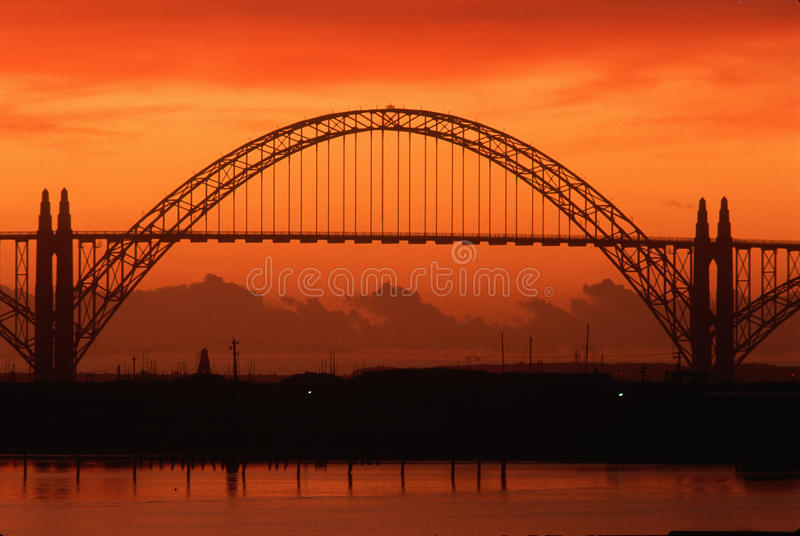 Silhouetted bridge. At sunset in Newport, Oregon royalty free stock photography
