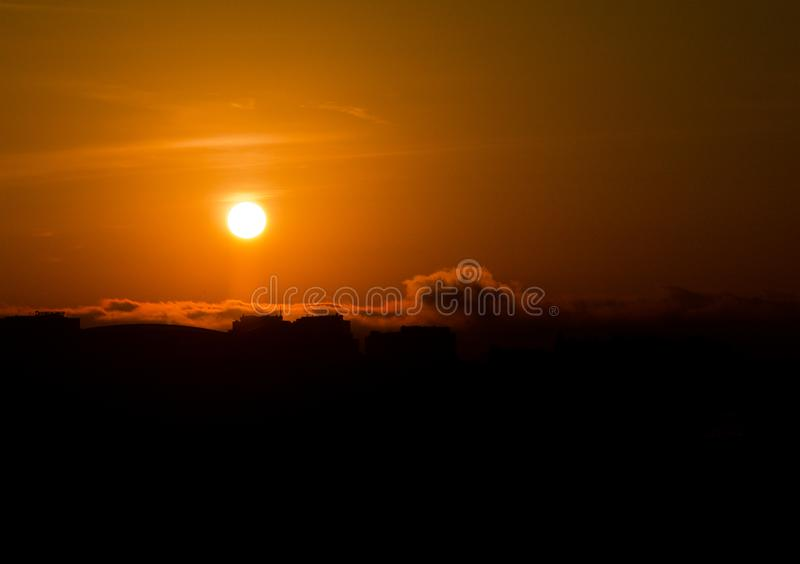 Silhouetted Building Tops at Sunset. Various silhouettes of building tops at sunset with hanging clouds rolling by royalty free stock photo