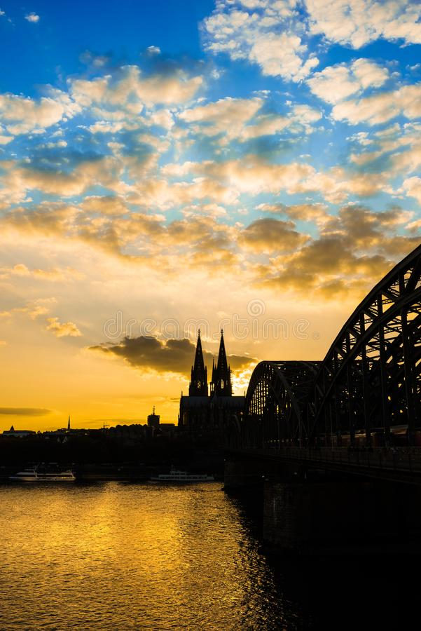 Cologne Cathedral and Hohenzollern Bridge at sunset royalty free stock photos