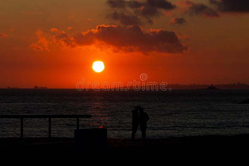 Silhouetted Couple at Sunset. A silhouetted couple stands at a pier during sunset royalty free stock image