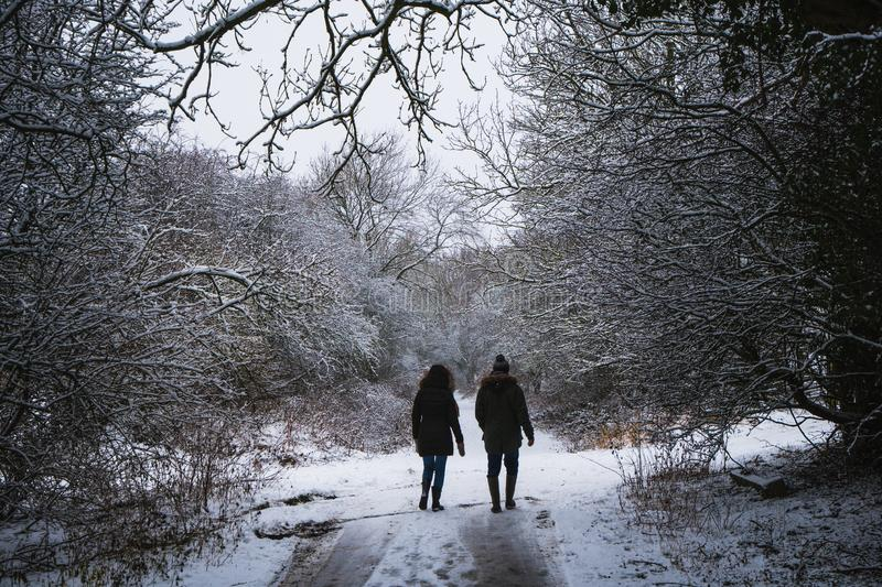 Silhouetted couple in the snow. A silhouetted couple walking in the white snow from behind stock photo