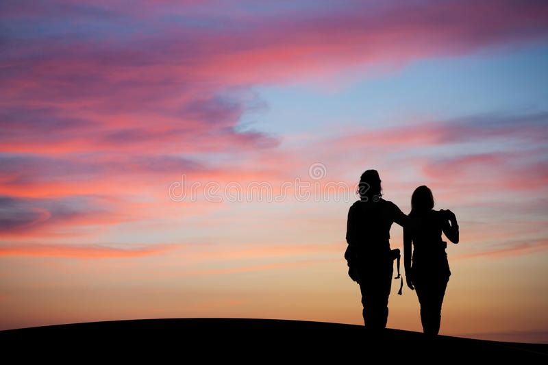 Silhouetted couple watching sunset sky. Silhouetted couple holding hands and watching sunset sky royalty free stock photos
