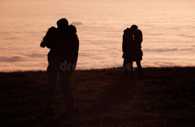Silhouetted couples kissing above inversion fog. In Black Forest, Germany royalty free stock image