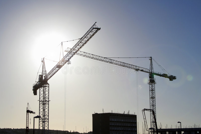 Silhouetted cranes royalty free stock photography