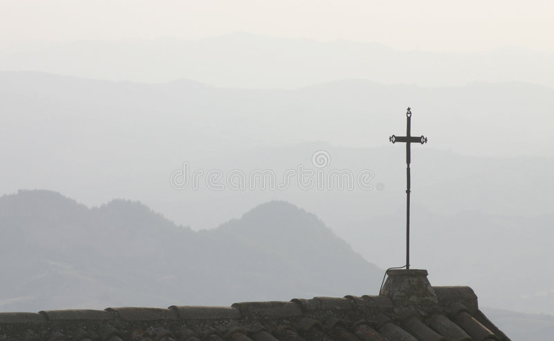 Silhouetted cross on rooftop