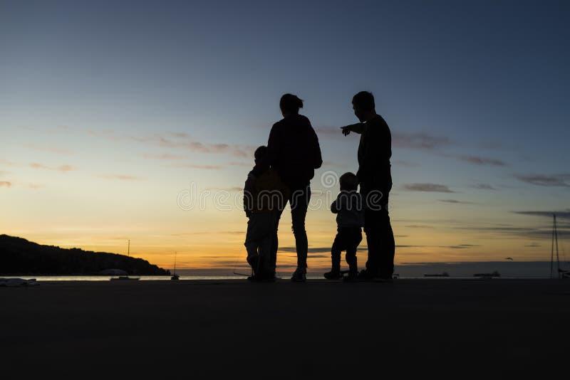 Silhouetted familj som ser utomhus solnedgången royaltyfri foto