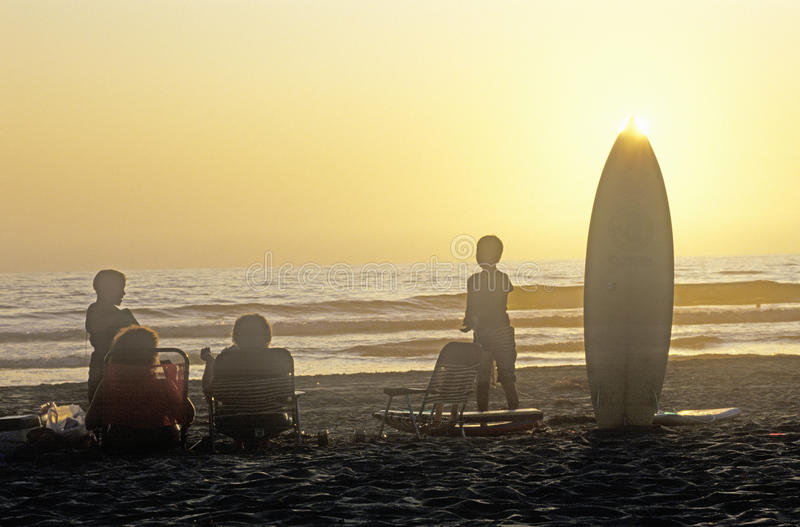 Silhouetted family on the beach at sunset, San Diego California royalty free stock photography