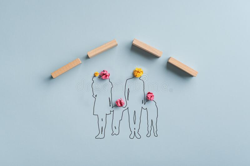 Silhouetted family under a roof made of wooden pegs royalty free stock photo
