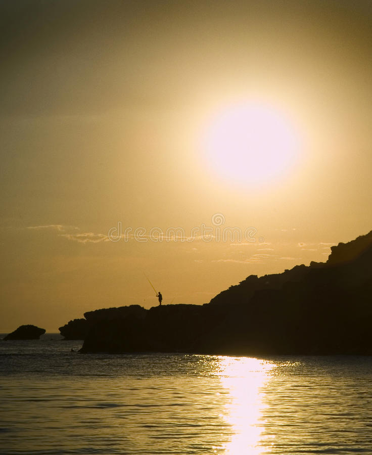 Silhouetted Fisherman. A lone fisherman silhouetted on the rocks with the yellow sun setting behind him royalty free stock photos