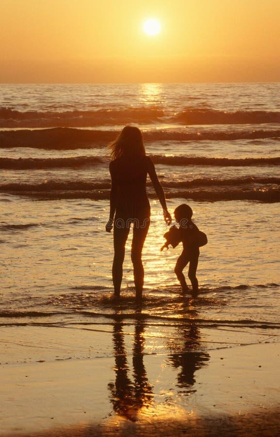 Silhouetted flicka och barn som går på stranden på solnedgången, San Diego, Kalifornien royaltyfria foton