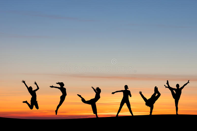 Silhouetted group tumbling and dancing in sunset stock image