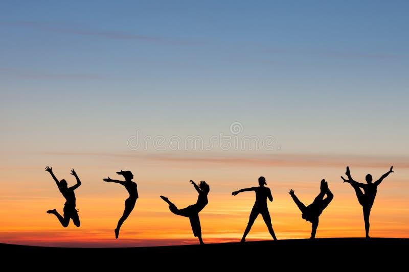 Silhouetted grupptumbling och dans i solnedgång fotografering för bildbyråer