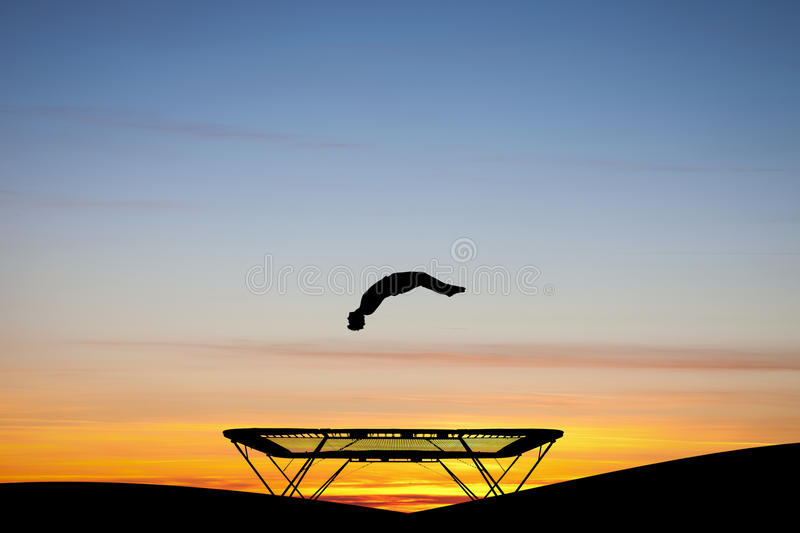 Silhouetted gymnast on trampoline. At sunset stock images