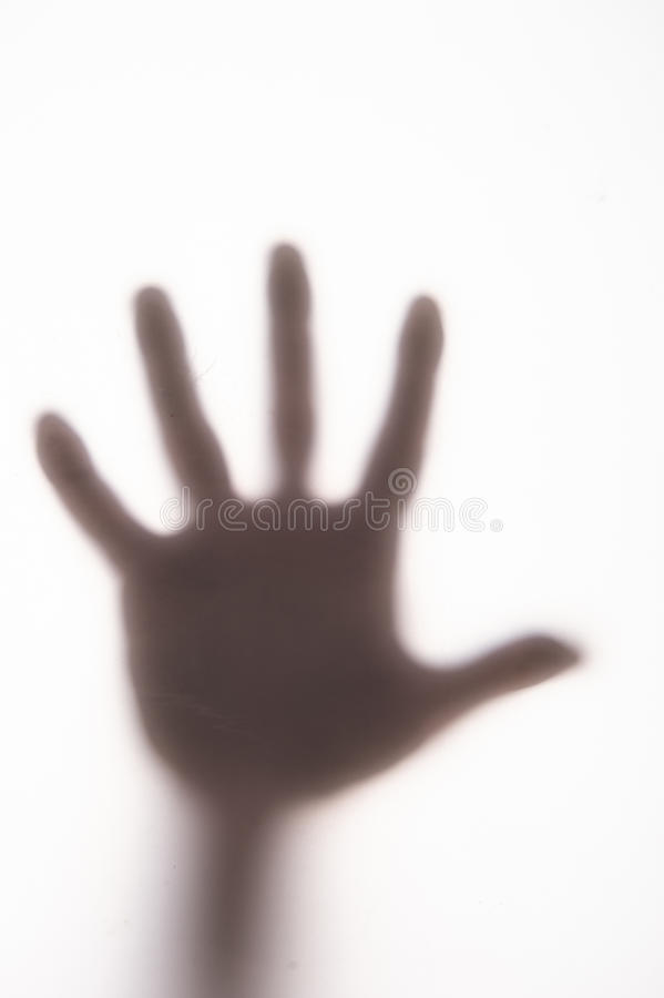 Silhouetted hand on frosted glass. stock photo