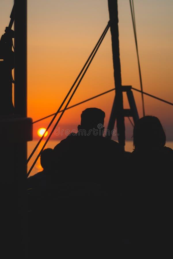Silhouetted koppla ihop på en soluppgångkryssning royaltyfri foto