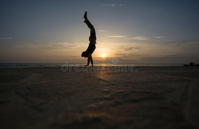 Silhouetted man doing handstand in sunset. At beach royalty free stock photos