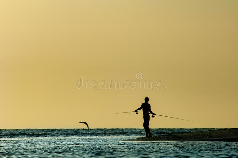 A silhouetted man fishes at sunset along Barefoot Beach, Florida. A silhouetted man fishes with two fishing rods at sunset along Barefoot Beach, Florida as a stock photos