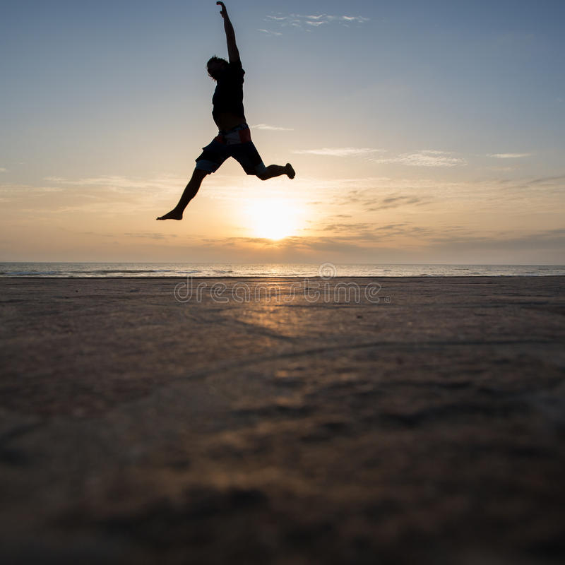 Silhouetted man jumping in sunset. At beach royalty free stock photos