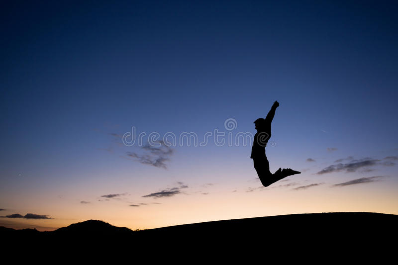Silhouetted man jumping in sunset. On hill royalty free stock images