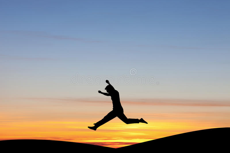 Silhouetted man jumping in sunset. In hills royalty free stock photography