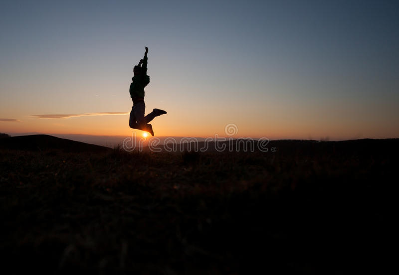 Silhouetted man jumping in sunset. In hills royalty free stock photo