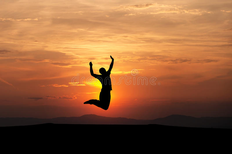 Silhouetted man jumping in sunset. Sky royalty free stock images
