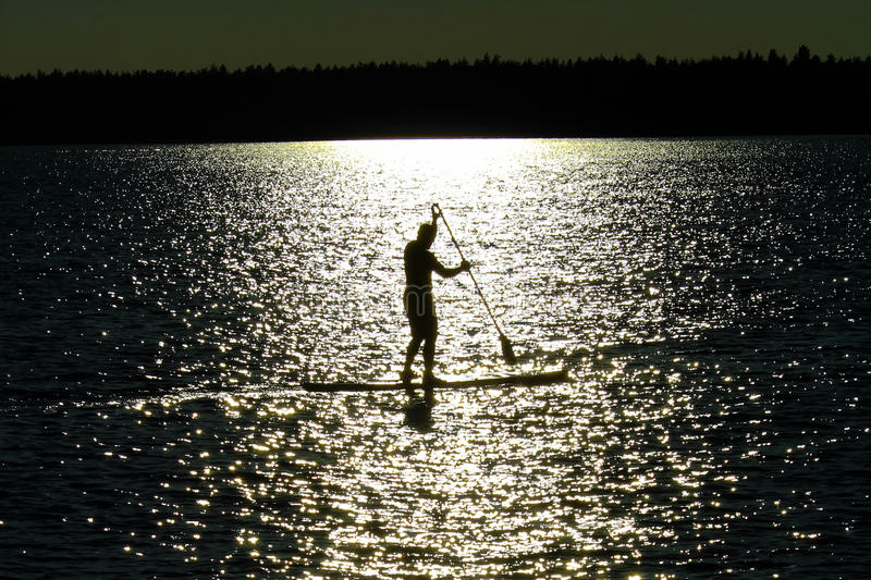 A silhouetted man paddle boarding on a Saskatchewan lake stock photos