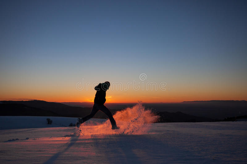 Silhouetted man running in winter landscape. Silhouette of man running in winter landscape through powder snow stock images
