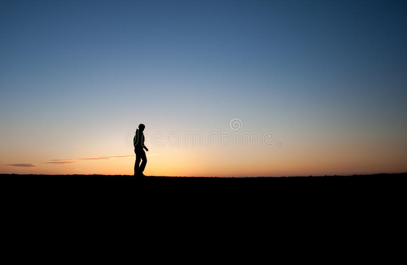Silhouetted man in sunset. Silhouetted man walking in sunset stock image