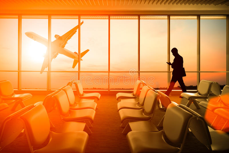 Silhouetted of man use mobile phone in airport at sunset. Business, connection and travel concept. stock image