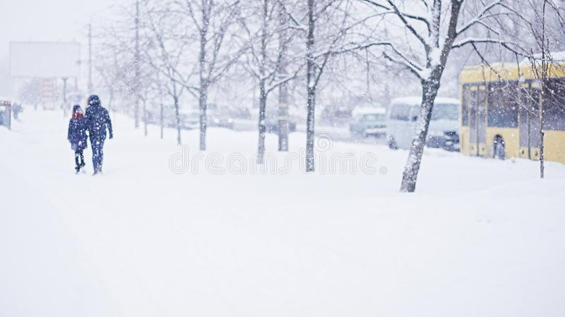 Abstract blurred people silhouettes walking along snowy street in winter. Heavy snowfall in the city. Blurred image of mother and royalty free stock images