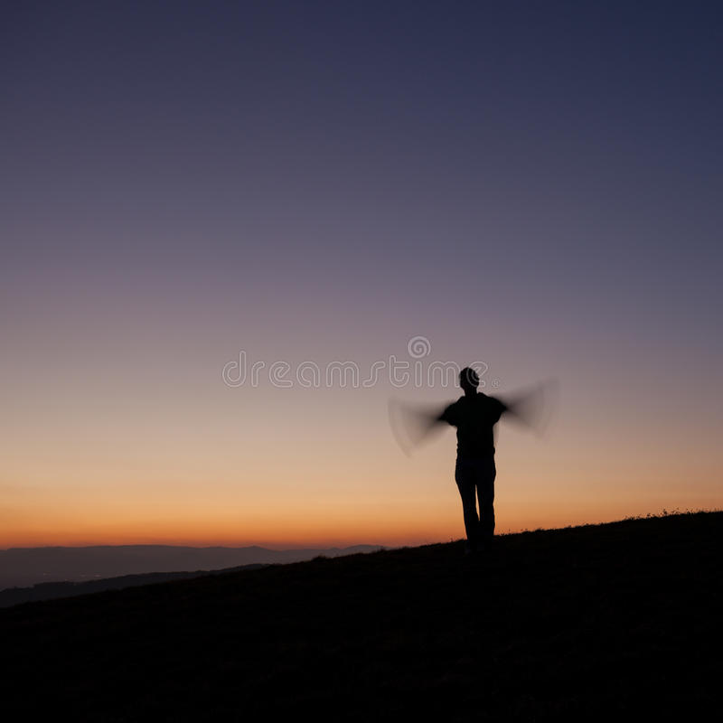 Silhouetted man waving with arms in sunset. Silhouette of man standing on hill and waving with arms royalty free stock photos