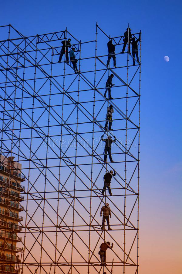 Silhouetted Men on metal stage scaffolding at dusk stock photography
