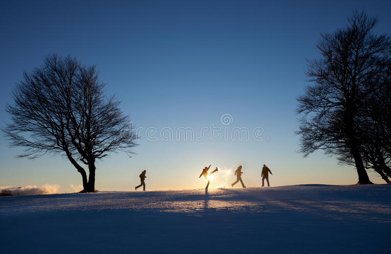 Silhouetted men running around in winter landscape. Silhouetted man running around in winter landscape on snow royalty free stock photo