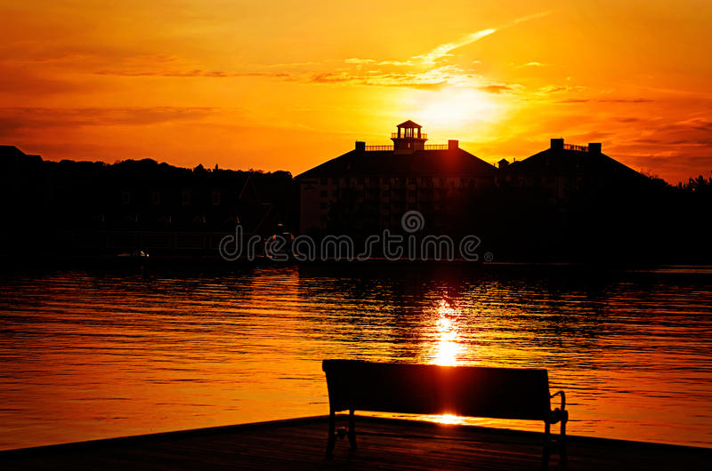 Silhouetted Park Bench By the Lake at Sunset stock photography