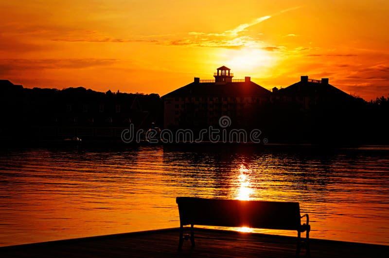 Silhouetted parkera bänken vid sjön på solnedgången arkivbild