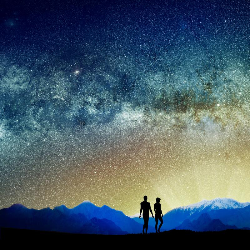 silhouetted people and lights of universe stock images