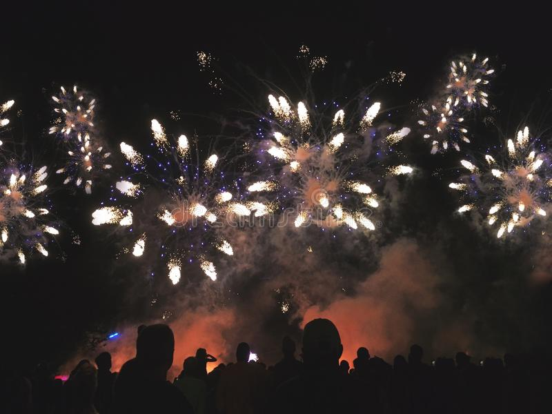 Silhouetted People Watching a Beautiful Fireworks Display stock image