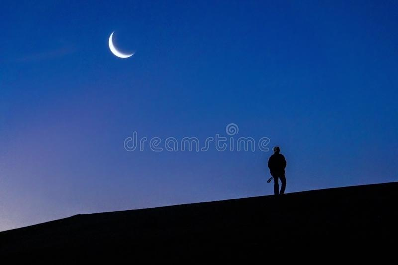 Silhouetted person walks by the hill with a camera and looking at young moon at Morning Twilights stock image
