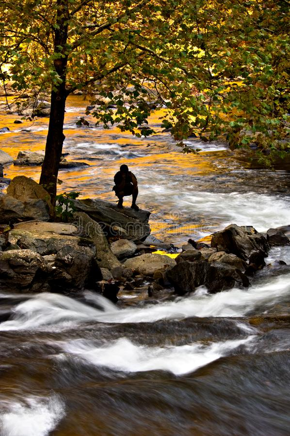 A silhouetted person watches the currents in a mountain river. A silhouetted person watches the currents in a mountain river surrounded by the bright colors of royalty free stock photography